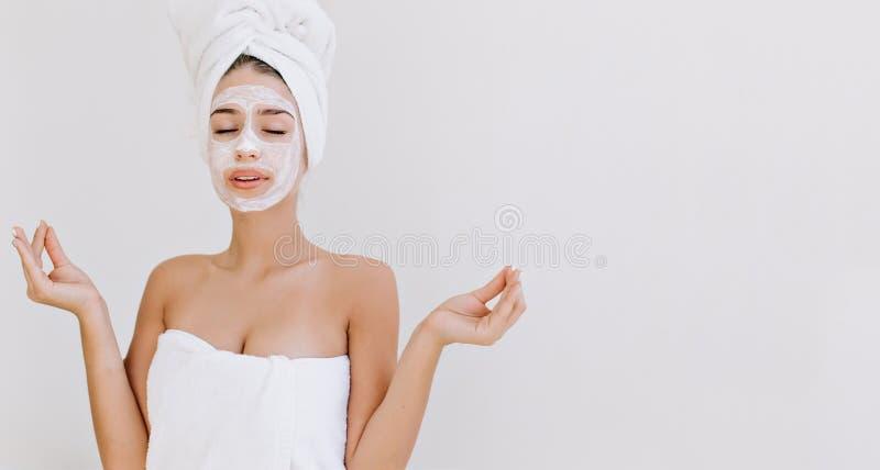 Portret piękna młoda kobieta z ręcznikami po tym jak wp8lywy skąpanie zrobi kosmetyk masce jej twarzy Odmładzanie, kosmetologia obraz stock