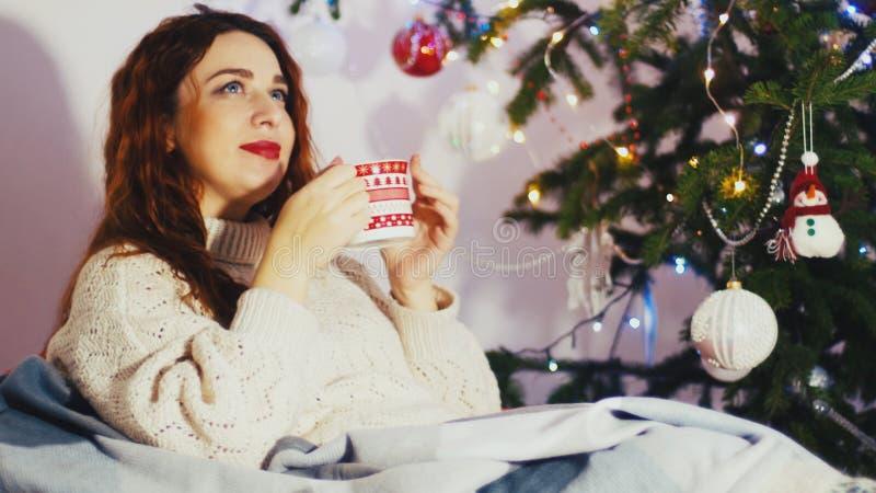 Portret piękna młoda miedzianowłosa kobieta jest ubranym eleganckiego boże narodzenie pulower i skarpety siedzi na wygodnej kanap zdjęcie royalty free