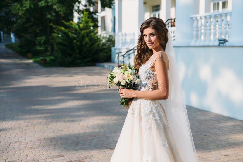 Portret piękna młoda panna młoda z ślicznym smite w białym ślubnej sukni chwyta bukiecie kwiaty w jej rękach Pojęcie fotografia stock