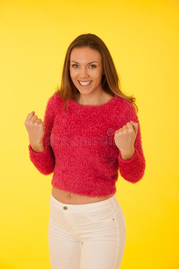 Portret piękna młoda szczęśliwa kobieta gestykuluje sukces w puszystym różowym pulowerze zdjęcie stock