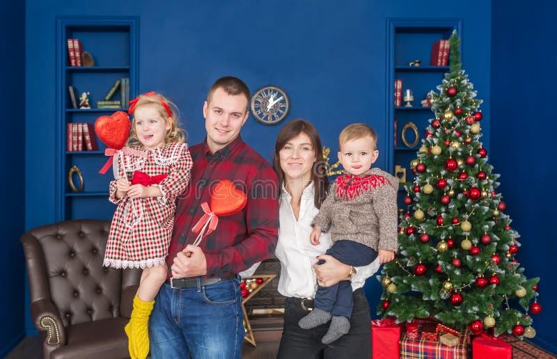 Portret piękna młoda szczęśliwa rodzina w Bożenarodzeniowych dekoracjach, salowy obrazy stock