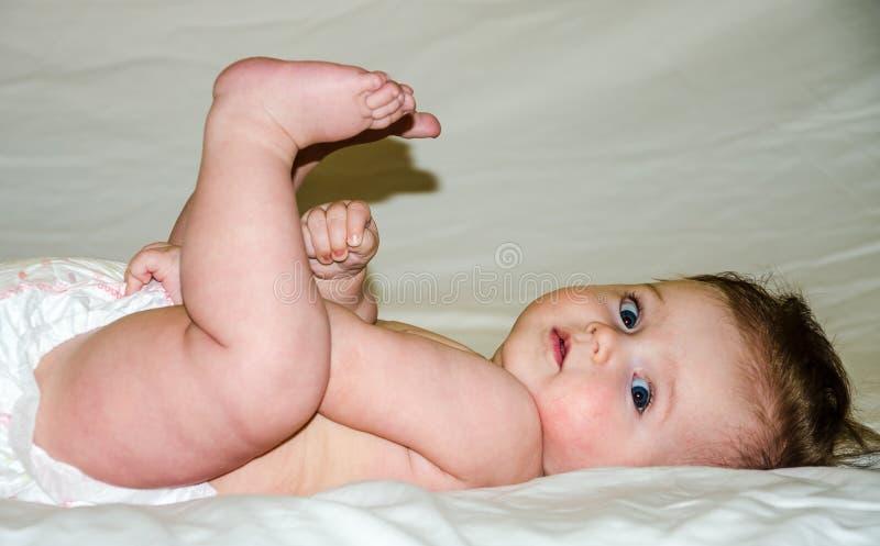 Portret piękna mała dziewczynka patrzeje daleko od jest kłamać nagi z jego ciekami i trzyma jego ręki pieluszkę obraz stock