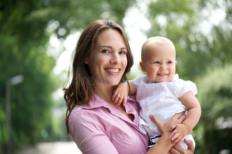 Portret piękna matka z uśmiechniętym dzieckiem outdoors fotografia royalty free