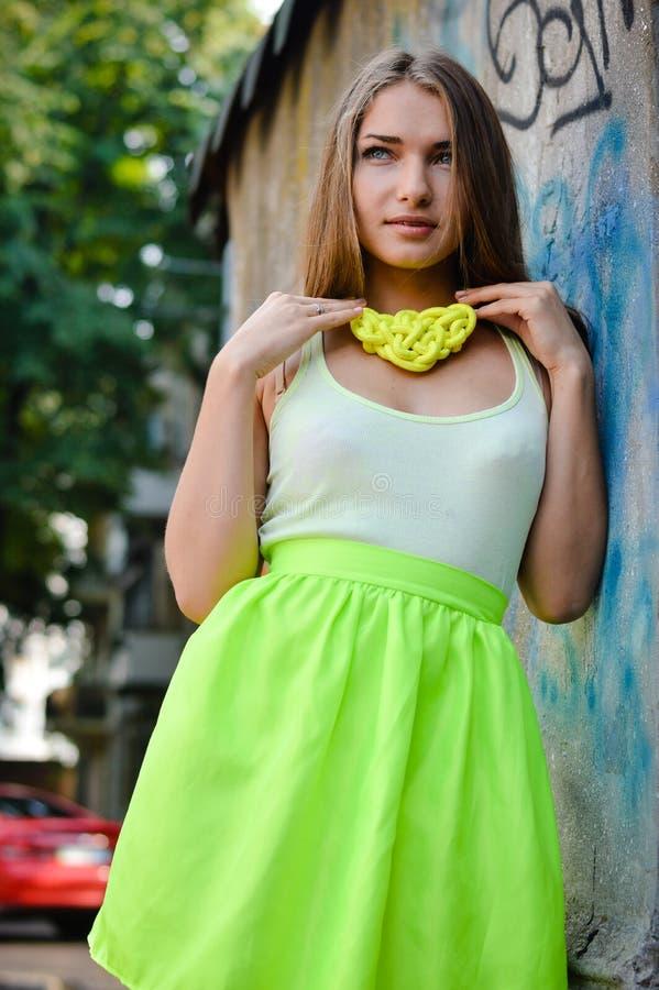 Portret piękna mody młoda dama ma zabawę delikatnie uśmiecha się kamerę nad graffiti miasta ścianą patrzeje i fotografia royalty free