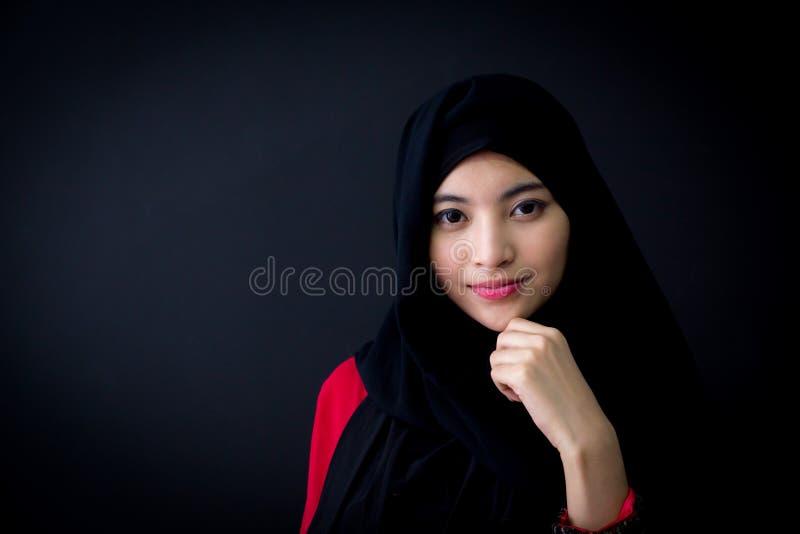 Portret piękna muzułmańska azjatykcia kobieta nad czarnym tłem z szczęśliwą muzułmańską kobietą obrazy royalty free