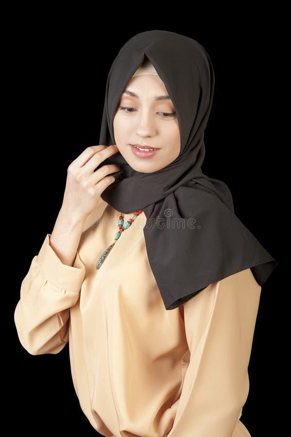 Portret piękna Muzułmańska kobieta w nowożytny orientalnym odziewa na odosobnionym czarnym tle zdjęcia stock