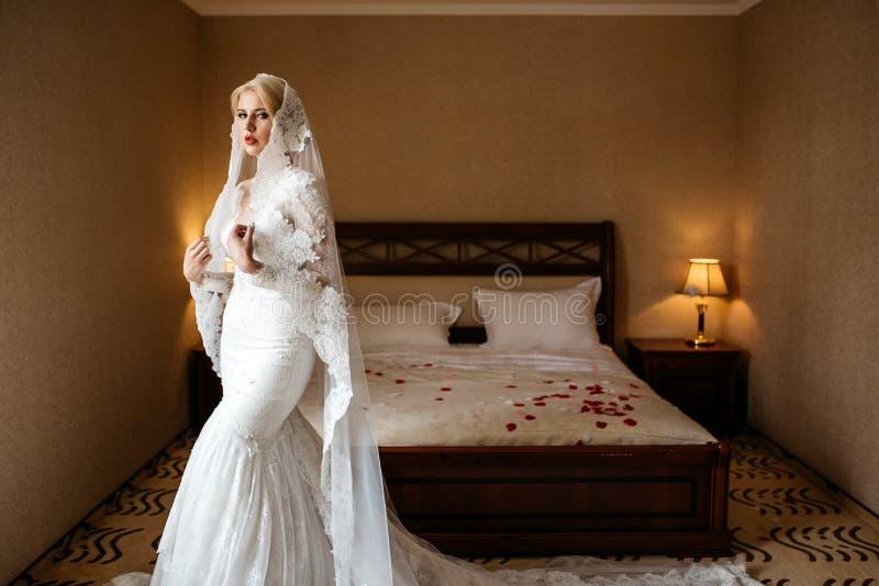 Portret piękna panna młoda w koronkowej ślubnej sukni i długiej przesłonie w pokoju hotelowym, obrazy stock