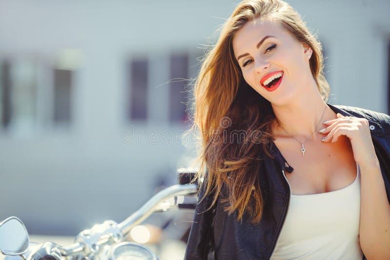 Portret piękna pogodna kobieta w mieście, ono uśmiecha się, jaskrawy naszły kolor, motocykl w tle obraz stock