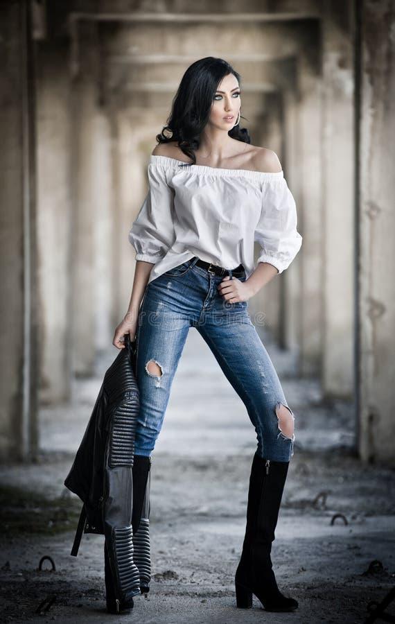 Portret piękna seksowna młoda kobieta z nowożytnym strojem, skórzaną kurtką, cajgami, białą bluzką i czerń butami, fotografia royalty free