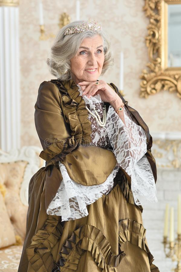Portret piękna starsza kobieta w smokingowej królowej, pozuje indoors obraz stock