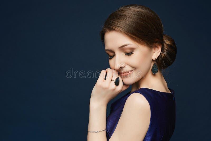 Portret piękna szczęśliwa brunetki dziewczyna przy błękitnym tłem fotografia royalty free
