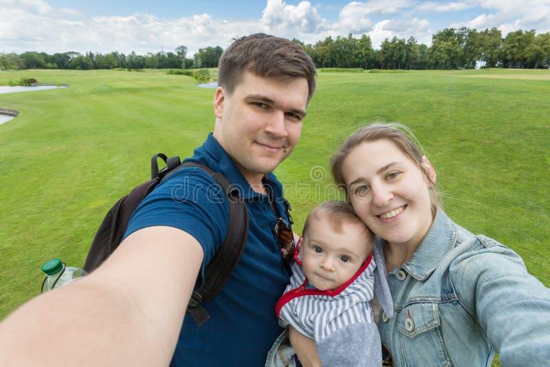 Portret piękna szczęśliwa rodzina z dzieckiem robi selfie przy pa zdjęcia stock
