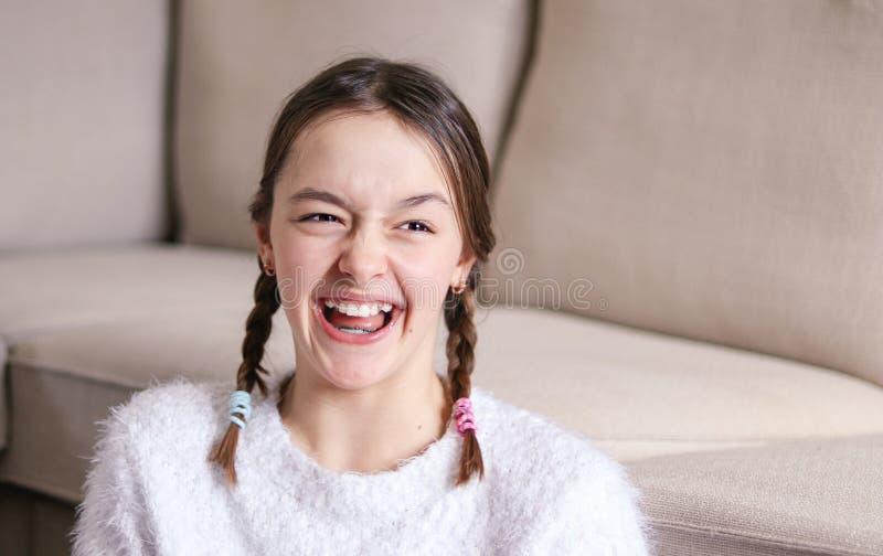 Portret piękna szczęśliwa roześmiana preteen dziewczyna z dwa pigtails w domu przeciw Kwiecień ptasim błękitny bąbla motylom kale fotografia stock