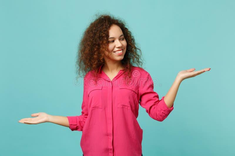 Portret piękna uśmiechnięta afrykańska dziewczyna patrzeje w przypadkowych ubraniach, wskazuje ręki na boku odizolowywać na błęki zdjęcie royalty free