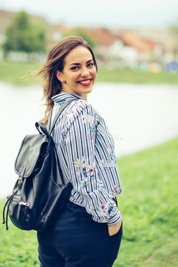 Portret piękna uśmiechnięta dziewczyna z plecakiem podczas gdy chodzący rzeką obraz stock