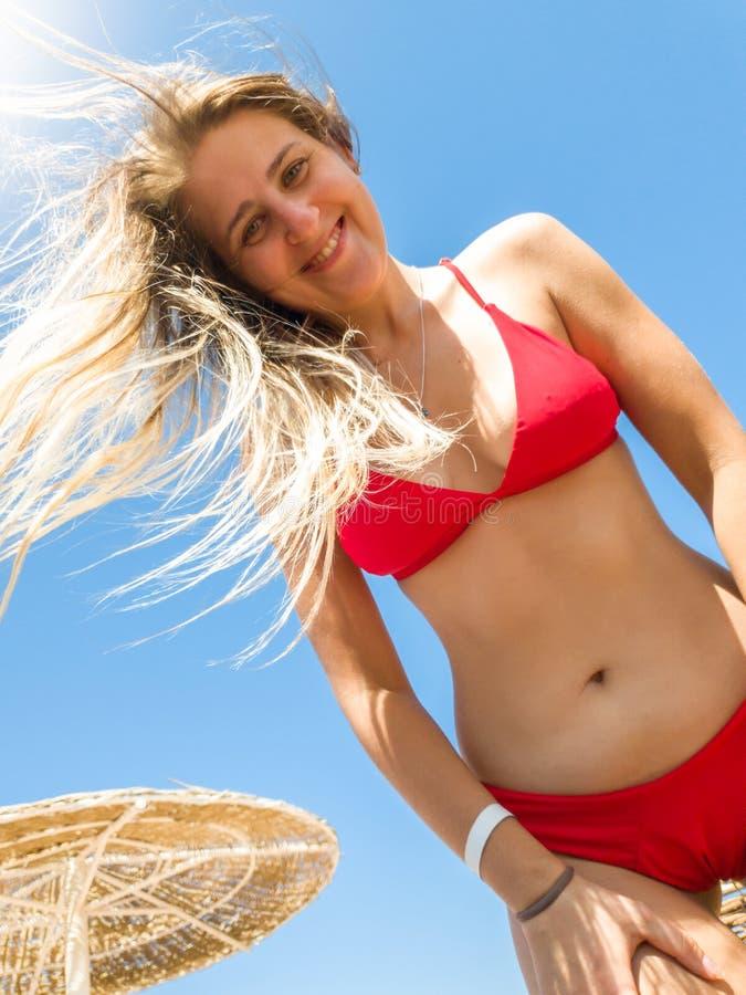 Portret piękna uśmiechnięta młoda kobieta z długie włosy jest ubranym czerwonym bikini pozuje na dennej plaży i patrzeje wewnątrz obrazy stock