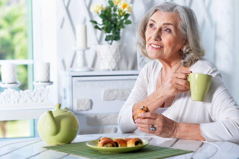 Portret piękna uśmiechnięta starsza kobieta pije herbaty podczas gdy siedzący przy kuchennym stołem obraz stock