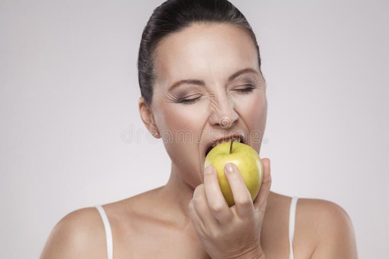 Portret piękna w średnim wieku kobieta z doskonalić twarzy skórą i zdrowi silni zęby jemy żółtego jabłka, odizolowywającego na po obraz royalty free
