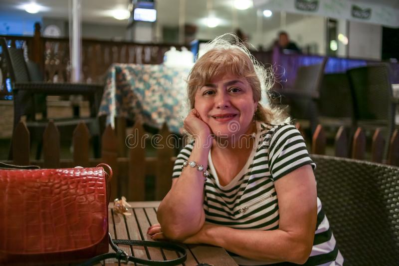 Portret piękna w średnim wieku kobieta z piękną postacią i duże piersi w pięknym lecie ubieramy obsiadanie w parku zdjęcie royalty free