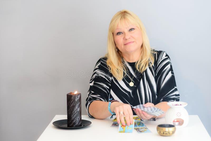 Portret piękna wiek średni kobieta siedzi blisko pomyślność narratora biurka z tarot świeczkami i kartami obraz stock