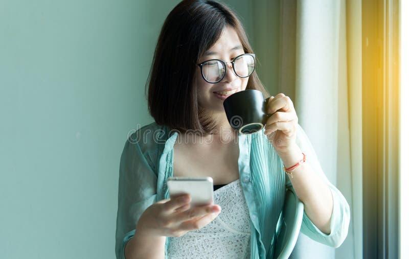 Portret piękne azjatykcie kobiety trzyma filiżanka kawy i używa telefon komórkowego na okno w domu w ranku i smi, Szczęśliwy fotografia stock