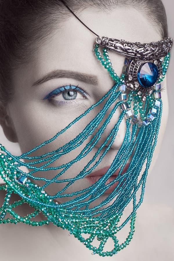 Portret piękne brunetki mody modela twarzy koloru skóry, błękit czerwieni i makeup białe wargi z błękitną biżuterią przed okiem i obraz royalty free
