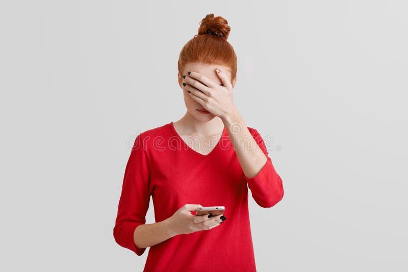 Portret piękne piegowate młodych kobiet pokrywy stawia czoło z ręką, uses nowożytny telefon komórkowy dla online komunikaci, odiz zdjęcia royalty free