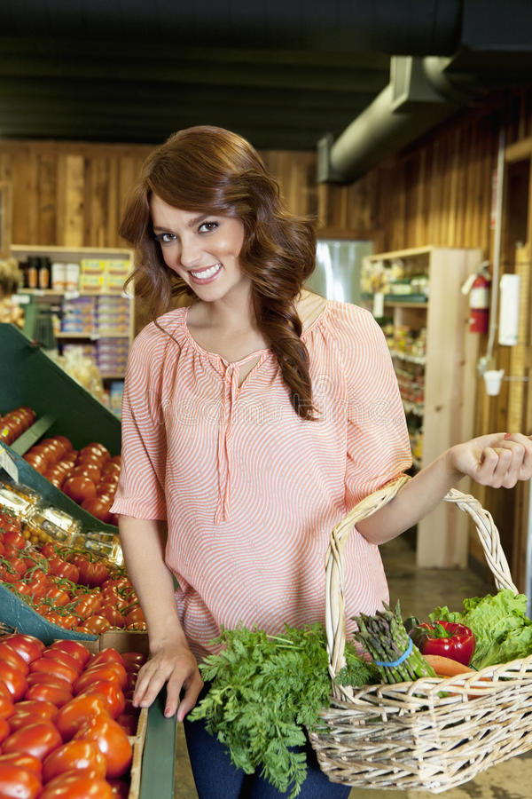 Portret pięknego brunetki mienia pomidoru koszykowy pobliski kram w rynku obrazy royalty free