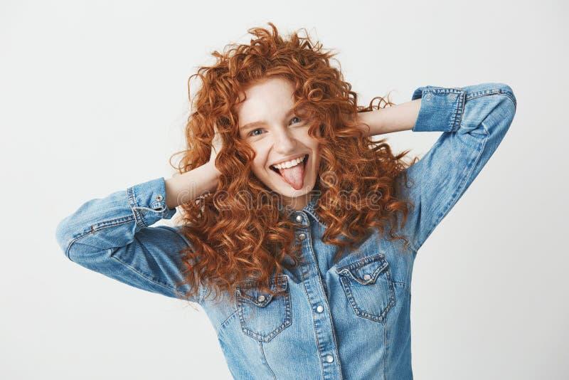 Portret pięknej imbirowej dziewczyny wzruszający włosiany ono uśmiecha się pokazuje jęzor patrzeje kamerę Biały tło zdjęcia stock
