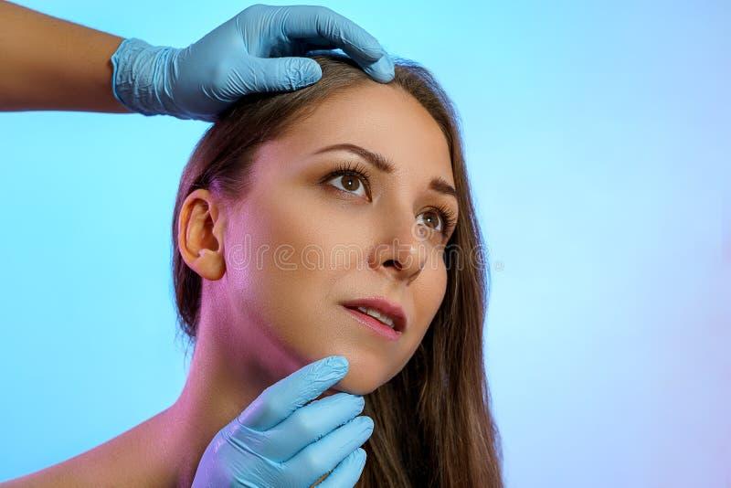 Portret pięknej młodej dziewczyny Ręce lekarzy w rękawiczkach medycznych badają twarz kobiety w celu wykonania zabiegów estetyczn obraz royalty free