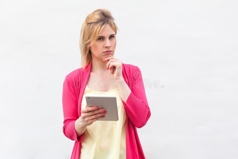 Portret piÄ™knej, przemyÅ›lanej biznesmenki, mÅ'odej kobiety w różowej bluzce, stojÄ…cej z tabletem, planujÄ…cej listÄ™ z zdjęcie stock