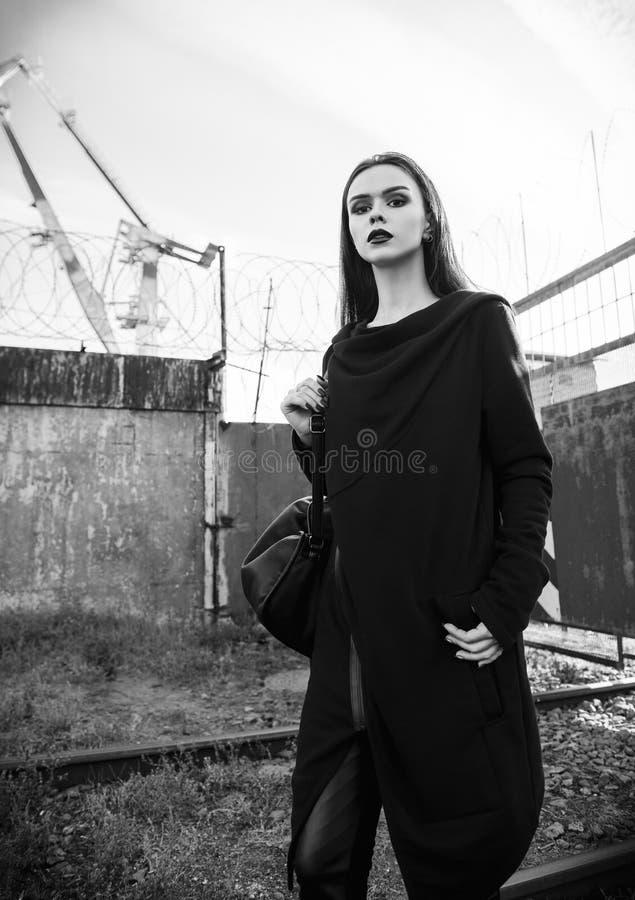Portret pięknej rockowej dziewczyny nieformalny model w tunice i skórze dyszy pozycję w przemysłowym terenie czarny white fotografia royalty free