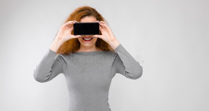 Portret pięknej rudzielec szczęśliwa uśmiechnięta młoda kobieta trzyma telefon komórkowego przed jej twarzą dalej w szarość ubran obrazy royalty free