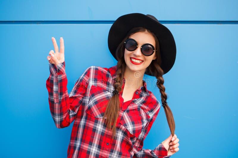 Portret piękno mody uśmiechnięta kobieta z warkocz fryzurą, robi pokojowi palcami w okularach przeciwsłonecznych na błękitnym tle fotografia royalty free