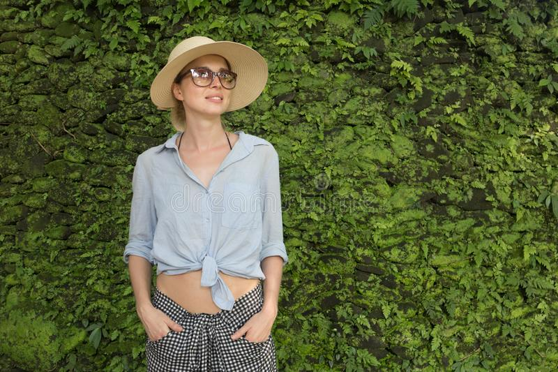 Portret piękny żeński podróżnik Uśmiechnięta młoda kobieta jest ubranym okulary przeciwsłonecznych w lato kapeluszu, stoi przed b obraz stock