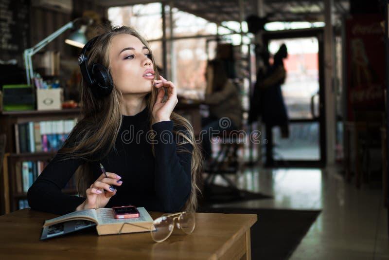 Portret piękny żeński uczeń słucha lub studiowanie linii kurs treningowy w hełmofonach, powabna młoda kobieta fotografia royalty free