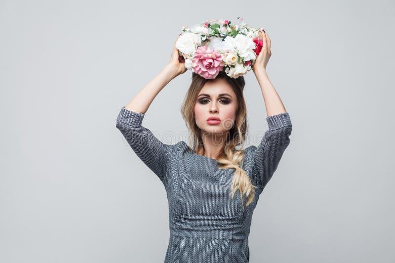 Portret piękny atrakcyjny moda model w popielatej sukni z makeup i fryzury pozycją, jest ubranym kierowniczych kwiaty i patrzeć fotografia royalty free
