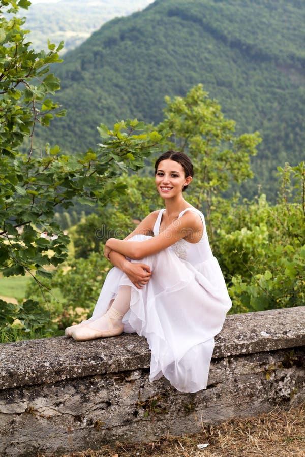 Portret piękny baletniczego tancerza obsiadanie na kamiennej ścianie fotografia stock
