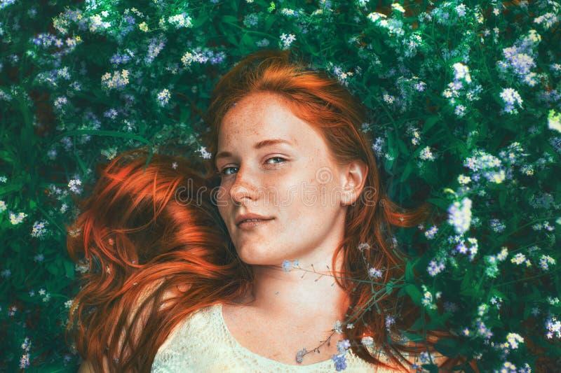 Portret piękny imbirowy dziewczyny obsiadanie na łące z niezapominajkowymi kwiatami obraz stock