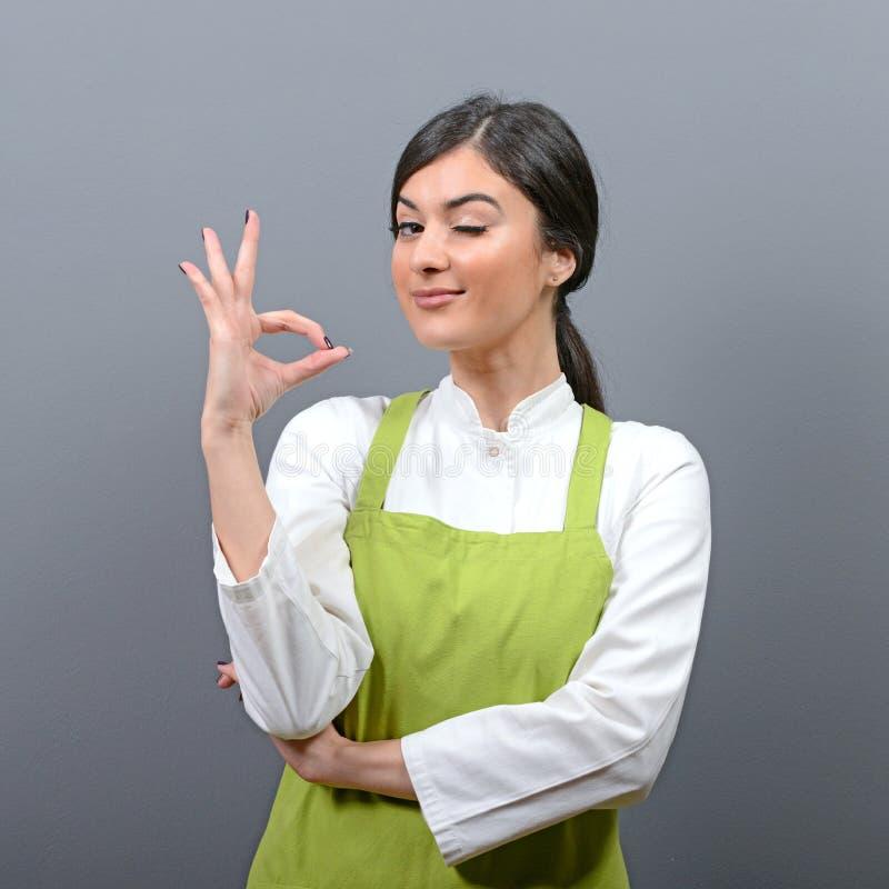 Portret piękny kobieta szef kuchni pokazuje ok znaka przeciw szaremu tłu zdjęcia stock