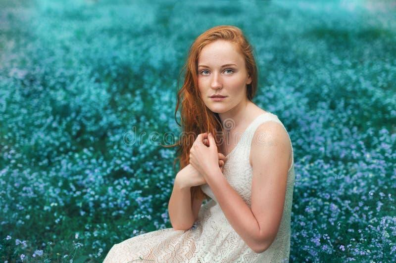 Portret piękny kobiety obsiadanie na łące z fotografia royalty free