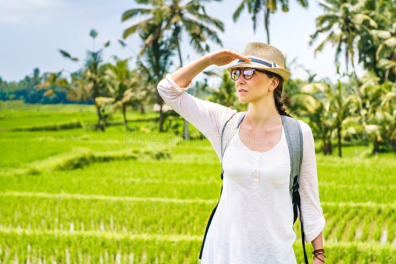 Portret piękny młoda dziewczyna podróżnik w kapeluszu, szkła, z plecaków spojrzeniami w odległość na ryżu polu, Bali Indonezja zdjęcie royalty free