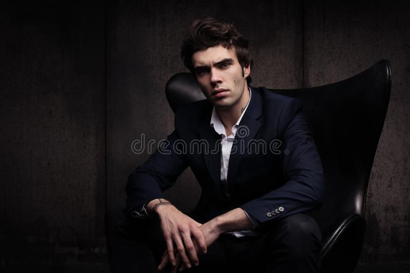 Portret piękny młodego człowieka obsiadanie w krześle Elegancki w pojawieniu zdjęcia royalty free