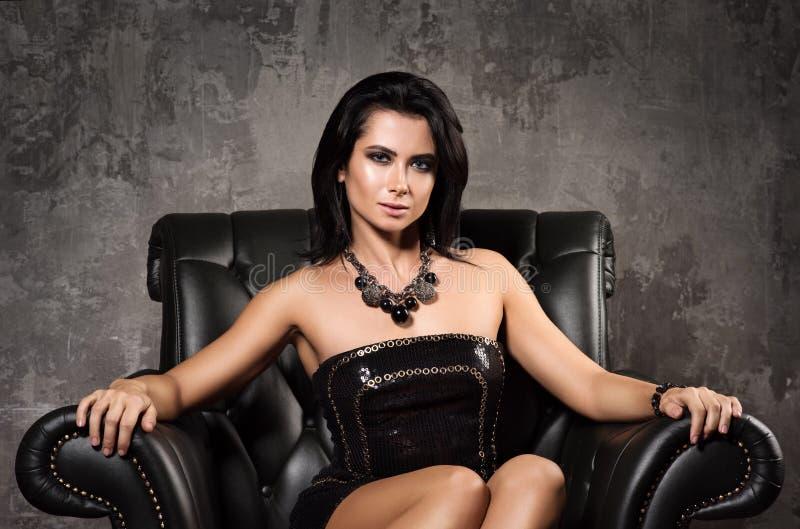 Portret piękny młodej kobiety obsiadanie w czarnym rzemiennym krześle obrazy royalty free