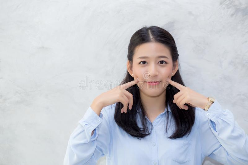 Portret piękny młody azjatykci kobiety szczęścia pozyci dotyka policzek na szarość cementu tekstury grunge ściany tle fotografia stock