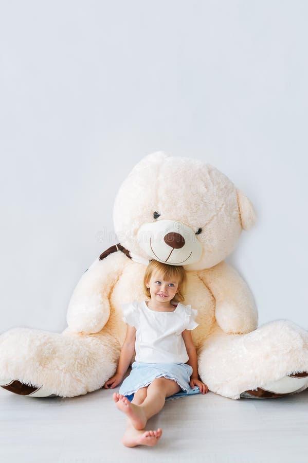 Portret piękny małej dziewczynki obsiadanie z ogromnym misiem obraz stock