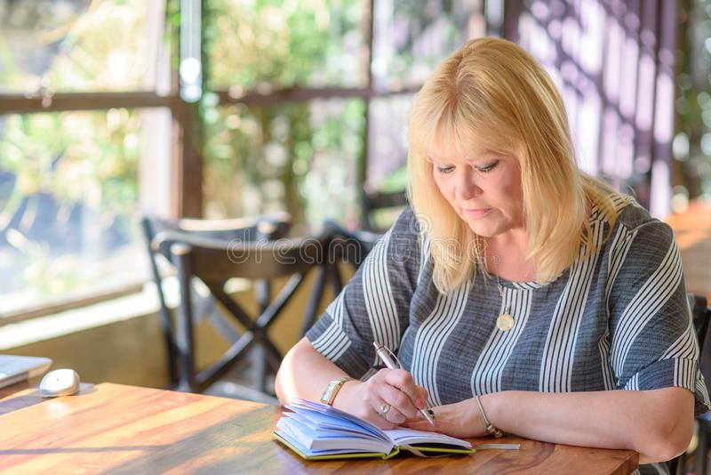 Portret piękny plus wielkościowa atrakcyjna starsza kobieta pisze dzienniczku w kawiarni zdjęcia royalty free
