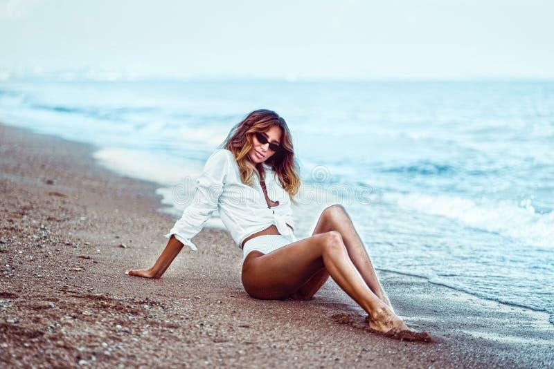 Portret piękny seksowny caucasian sunbathed kobieta w okularach przeciwsłonecznych z długie włosy w swimsuit lying on the beach n obraz stock