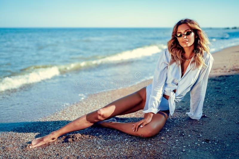 Portret piękny seksowny caucasian sunbathed kobieta w okularach przeciwsłonecznych z długie włosy w swimsuit lying on the beach n obrazy royalty free