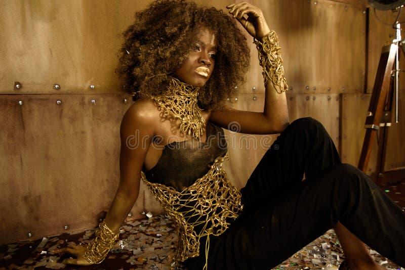 Portret piękny seksowny elegancki młody afrykański kobieta model z perfect czystą skórą w czerni i złocie odziewa pozować na podł zdjęcie royalty free